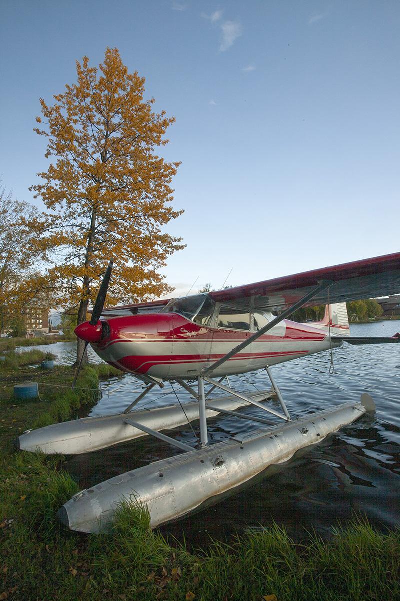 a Cessna floatplane at a shore on pontoons