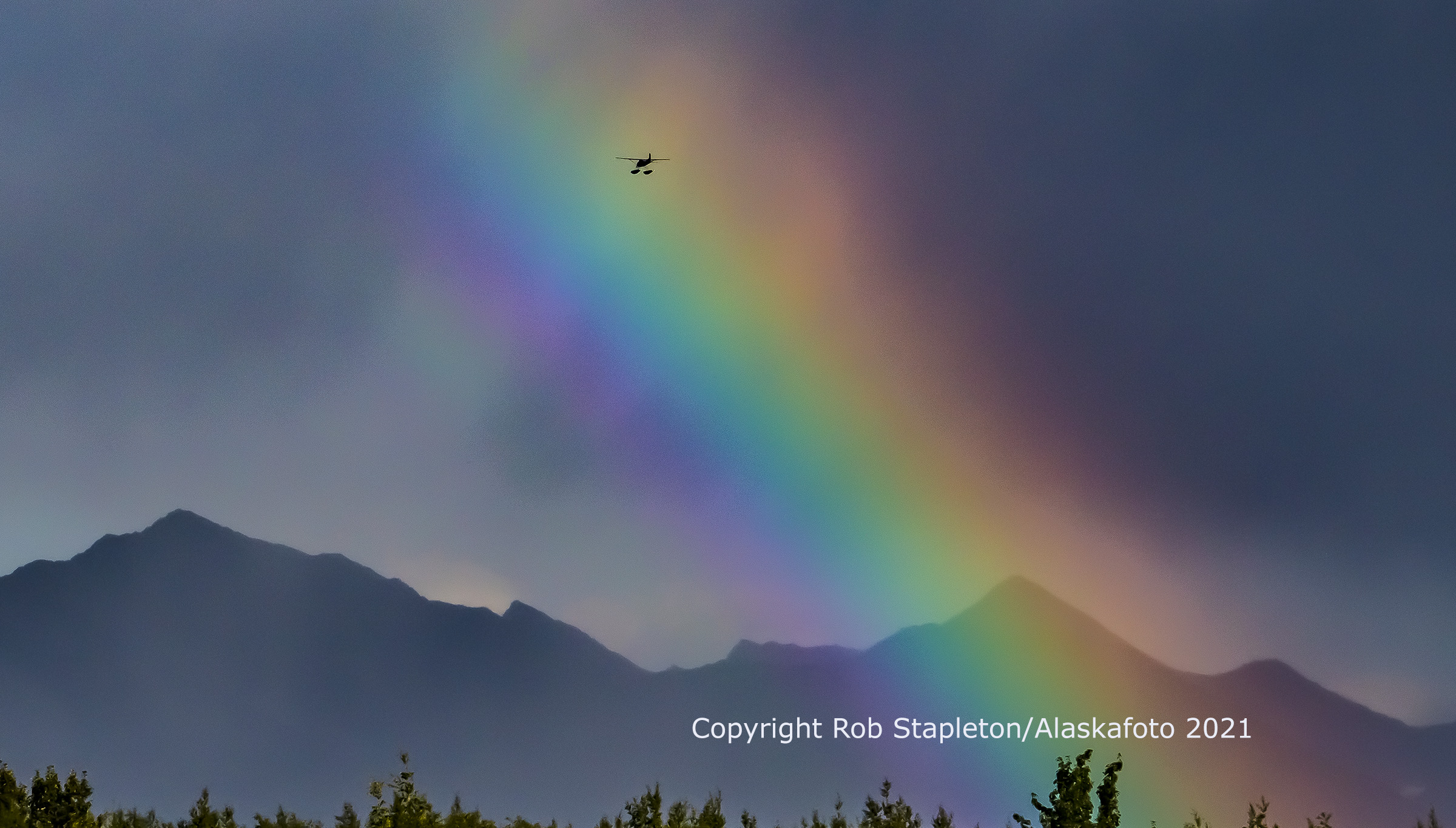Arc of a rainbow with an aircraft flying through it