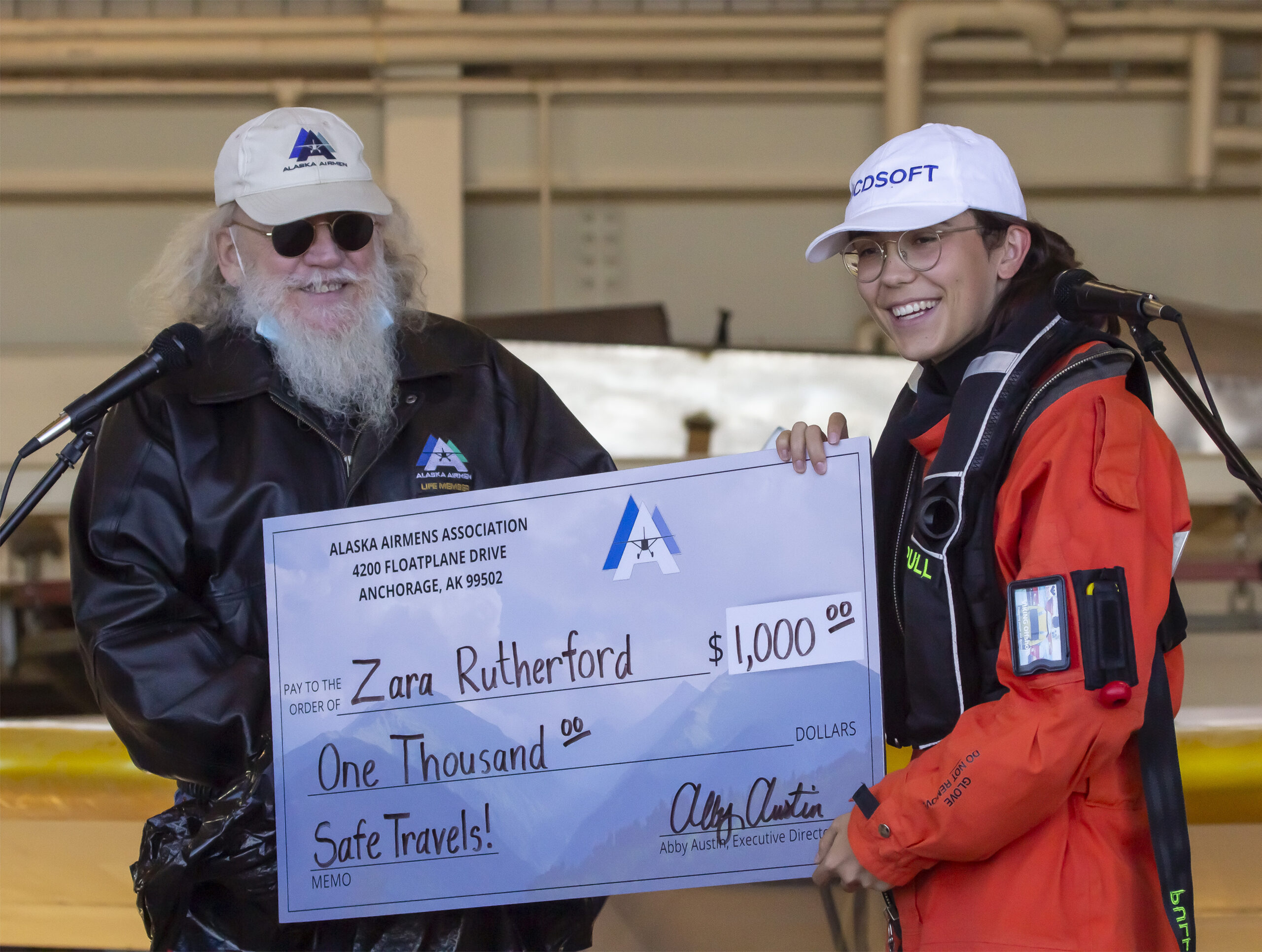 John Dahlen, right and Zara Rutherford right with a check for one thousand dollars USD